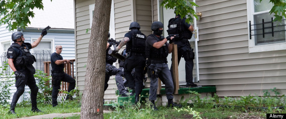 Police from tactical team making entry to serve a high-risk drug related search warrant. Street Narcotics Unit.