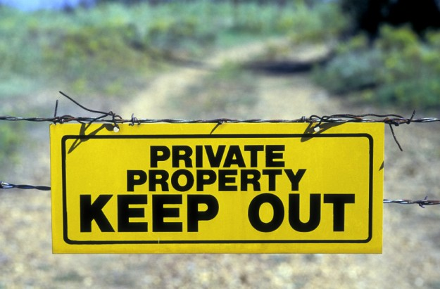 "A yellow and black ""Private Property Keep Out"" sign attached to a barbed wire gate stretched across a dirt road."