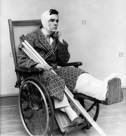 1930s-man-in-wheelchair-leg-cast-bandage-head-neck-crutches-aakm3g
